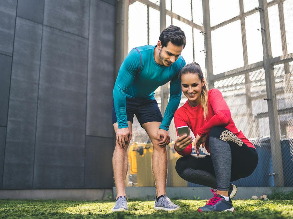 Mann und Frau sind beim Fitnesstraining und schauen sich auf Smartphone eine Fitness-App an