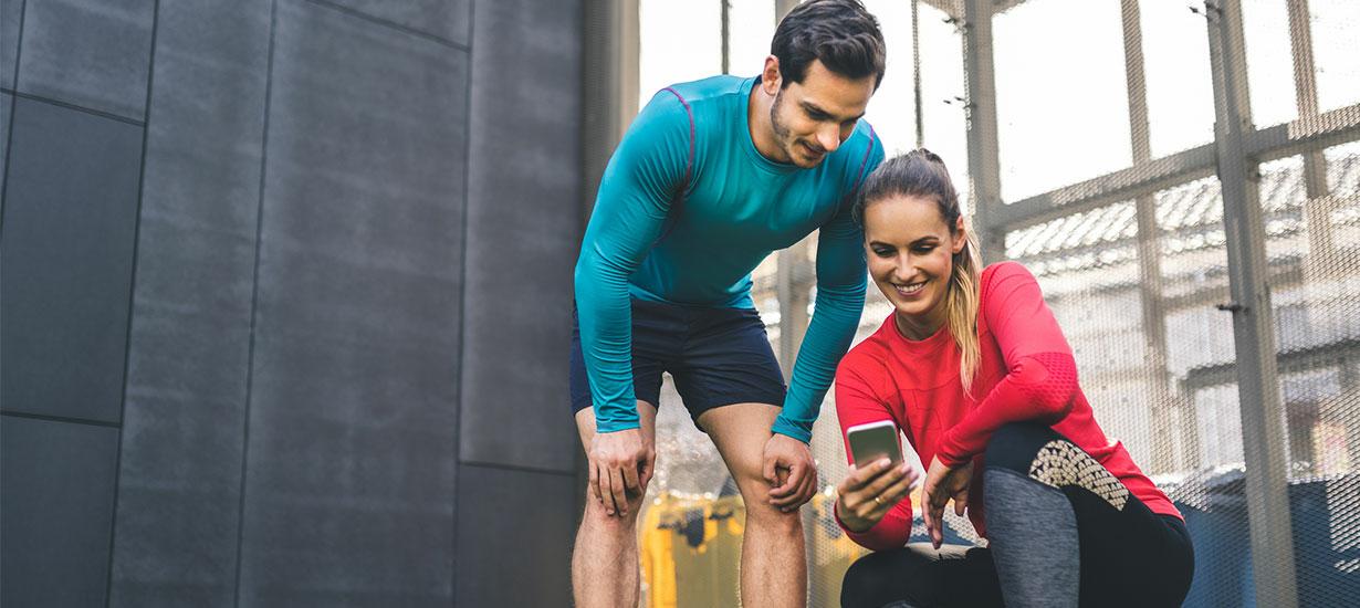 Mann und Frau schauen sich beim Fitnesstraining eine App auf ihrem Smartphone an